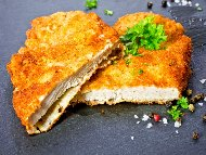 Хрупкави пържени пилешки шницели от филе в панировка от хлебни трохи с пармезанова коричка на тиган